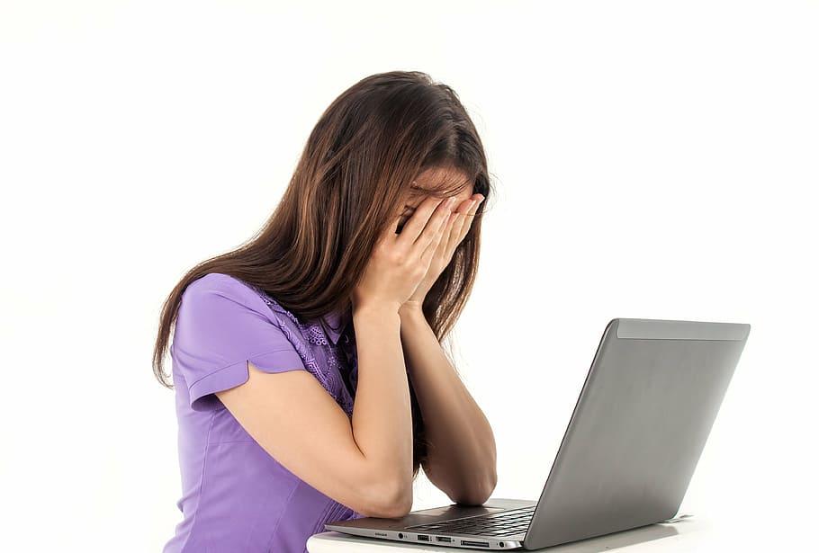 Frau vor einem Notebook. Hält sich frustriert die Hände vor ihr Gesicht.